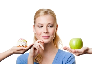 Beautiful woman makes a tough choice between cake and apple, iso